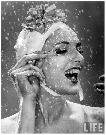 woman-wearing-flowered-bathing-cap-applying-mascara-as-water-showers-around-her-1946-gjon-mili
